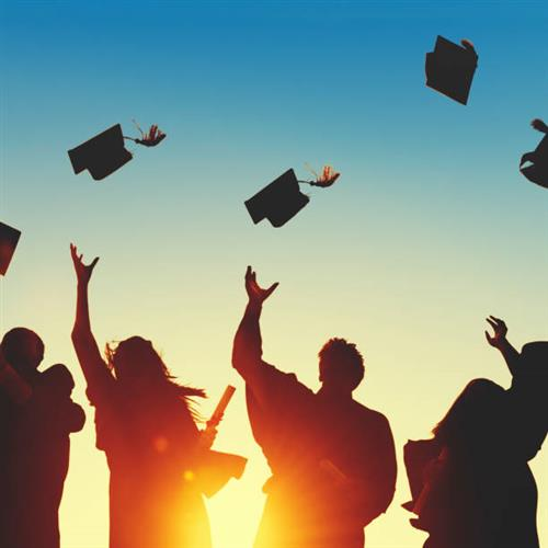 Silhouette of graduates tossing caps in air.